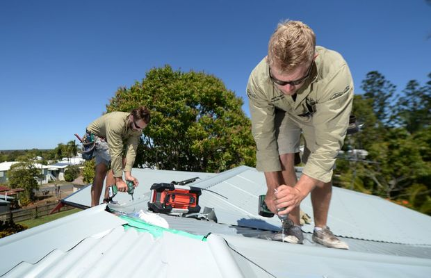 PHOTO CREDIT: THE MORNING BULLETIN Nick Phillips owner/manager of Flashpro Roofing (right) with Sam Smith putting the finishing touches on a new roof after the old asbestos one was replaced.